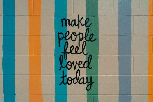 """Graffiti on the wall saying """"Make People Feel Loved Today"""""""